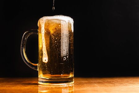 Cold beer with foam in a mug, on a wooden table and a dark background with blank space for  text. Stock Photo mug of cold foamy beer close-up. Standard-Bild - 134080678