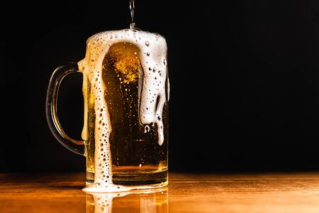 Cold beer with foam in a mug, on a wooden table and a dark background with blank space for  text. Stock Photo mug of cold foamy beer close-up. Standard-Bild - 134080699