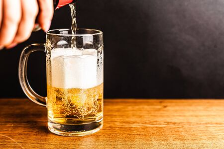 Cold beer with foam in a mug, on a wooden table and a dark background with blank space for  text. Stock Photo mug of cold foamy beer close-up. Standard-Bild - 134080725