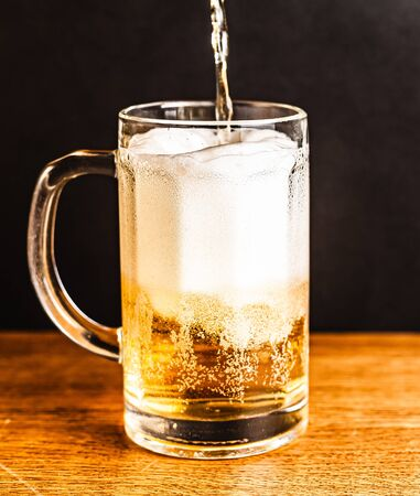 Cold beer with foam in a mug, on a wooden table and a dark background with blank space for  text. Stock Photo mug of cold foamy beer close-up. Standard-Bild - 134080733
