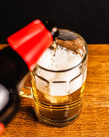 Cold beer with foam in a mug, on a wooden table and a dark background with blank space for  text. Stock Photo mug of cold foamy beer close-up. Standard-Bild - 134080744