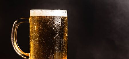 Cold beer with foam in a mug, on a wooden table and a dark background with blank space for  text. Stock Photo mug of cold foamy beer close-up. Standard-Bild - 134080748