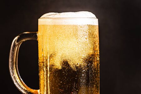 Cold beer with foam in a mug, on a wooden table and a dark background with blank space for  text. Stock Photo mug of cold foamy beer close-up. Standard-Bild - 134080755