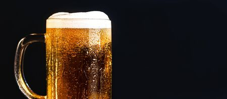 Cold beer with foam in a mug, on a wooden table and a dark background with blank space for  text. Stock Photo mug of cold foamy beer close-up. Standard-Bild - 134080758