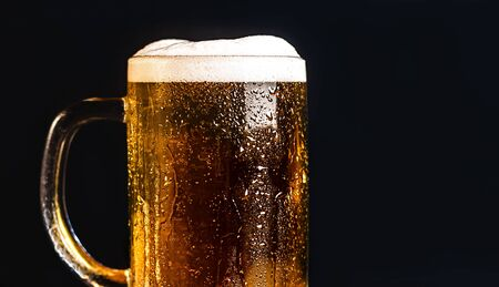 Cold beer with foam in a mug, on a wooden table and a dark background with blank space for  text. Stock Photo mug of cold foamy beer close-up. Standard-Bild - 134080760
