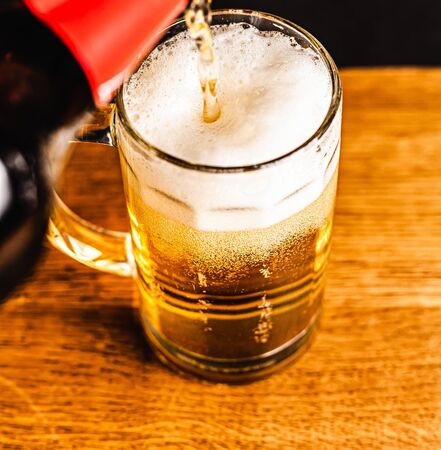 Cold beer with foam in a mug, on a wooden table and a dark background with blank space for  text. Stock Photo mug of cold foamy beer close-up. Standard-Bild - 134080770
