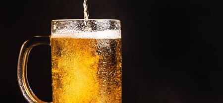 Cold beer with foam in a mug, on a wooden table and a dark background with blank space for  text. Stock Photo mug of cold foamy beer close-up. Standard-Bild - 134080774