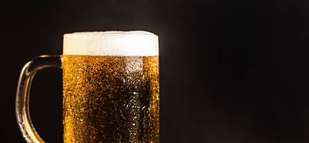 Cold beer with foam in a mug, on a wooden table and a dark background with blank space for  text. Stock Photo mug of cold foamy beer close-up. Standard-Bild - 134080776