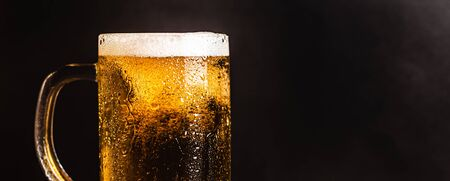 Cold beer with foam in a mug, on a wooden table and a dark background with blank space for  text. Stock Photo mug of cold foamy beer close-up. Standard-Bild - 134080777