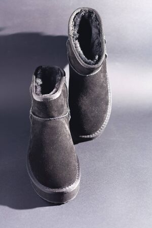 Black suede uggs. Stock photo on a black background. Stockfoto