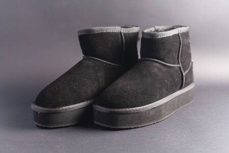 Black suede uggs. Stock photo on a black background. 免版税图像