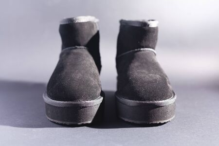 Black suede uggs. Stock photo on a black background. Stok Fotoğraf