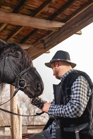 Portrait of a guy in a hat with a black horse.