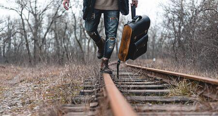 Facet w zamszowych jesiennych butach na kolei. Pojęcie turystyki pieszej, praktyczne ubrania podróżne, buty.