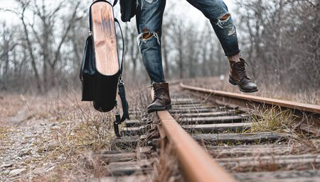 A guy in suede autumn boots on the railway. The concept of hiking, travel practical clothes, shoes. Zdjęcie Seryjne