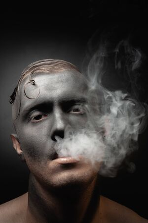 Close-up portrait of a handsome guy in makeup blows smoke. Stock art photo of a smoker.