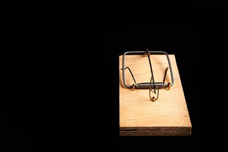 Mousetrap without bait isolate on a black background. Stock photo traps. Foto de archivo