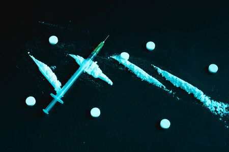 Different drugs on a dark background. Stock photo addiction concept.