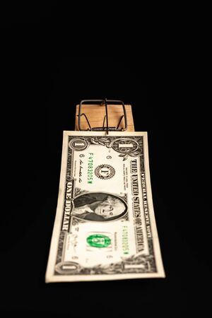 Dollar in a mousetrap on a black background. The bait in the form of money.