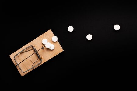 Mousetrap with bait in the form of a tablets. Stock Photo Addiction / dependence concept.
