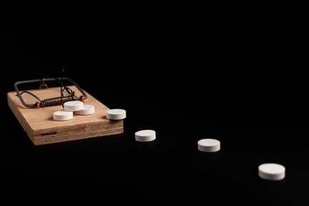 Mousetrap with bait in the form of a tablets. Stock Photo Addiction  dependence concept.