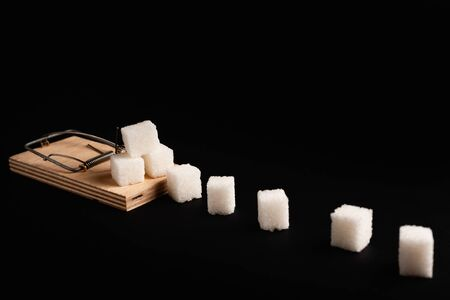 Stock photo of a mousetrap with a bait in the form of sugar. Sugar consumption diseases concept.