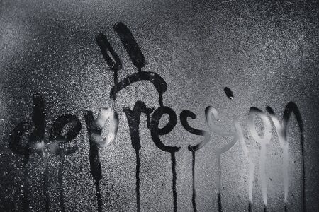 """Window with raindrops. Stock photo the inscription """"depression"""" in wet glass."""