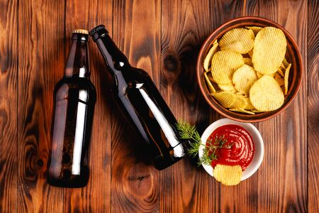 Two glass bottles of beer without a label with a snack in the form of potato chips with red sauce. Stock photo beer with snack on a wooden table, top view.