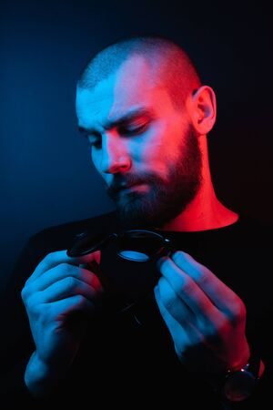 Brutal portrait neon style. Portrait of the face of a charismatic guy with a beard. Stock Photo