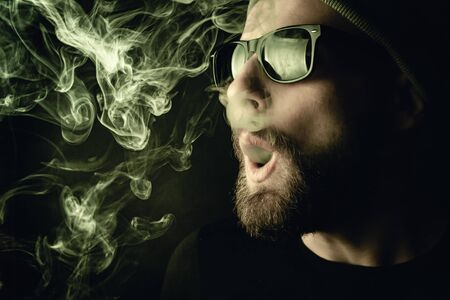 Portrait of a bearded, white hipster smoker on a dark background. Studio stock photo concept of smoking cigarettes and marijuana.
