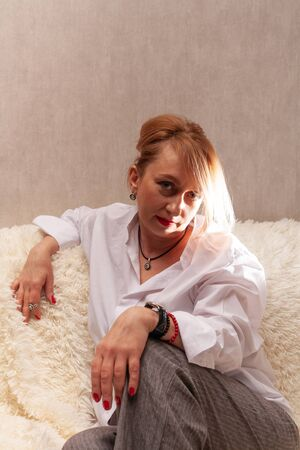 Portrait of an attractive middle-aged woman. Homemade portrait on the couch, middle-aged blonde. 免版税图像