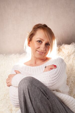 A beautiful adult woman is sitting in a room on a sofa. Portrait of a blonde at home.