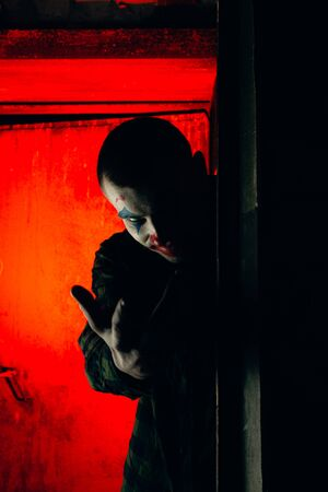 Close-up portrait of a joker man. Stock photo makeup joker in a horror room.