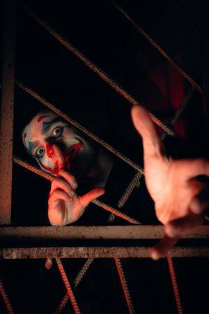Close-up portrait of a joker man. Stock photo makeup joker in a horror room.