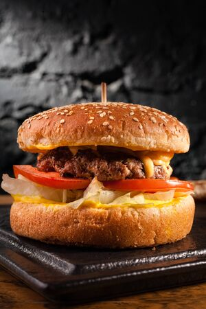 Meat burger on black wall background, side view.