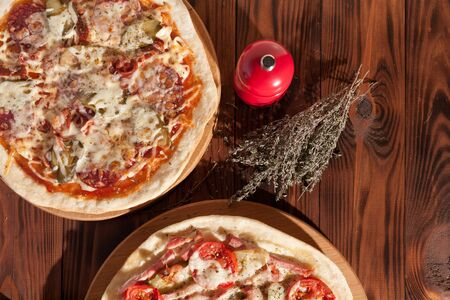 Ready-made appetizing pizza close-up. Stock photo pizza on a wooden table.