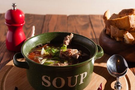 Rustic meat bone soup / broth sprinkled with green onions on a wooden table with crackers.