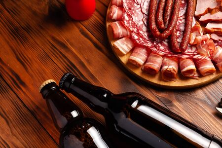 Beer snack in the form of meat products and bottled beer. Appetizer in the form of slicing bacon, salami, ham, hunting sausages. Stock photo beer and snack on a wooden table.