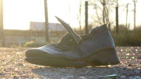An old boot in the midst of urban trash, lie on the pavement under the rays of a sunny day.