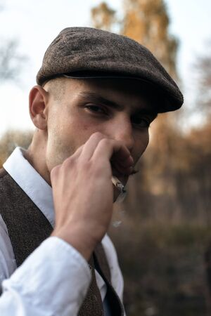 Retro 1920s portrait of an English gangster with a flat cap. Smokes a cigarette on the street..
