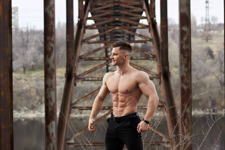Attractive young guy demonstrates muscular torso outdoors. Beautiful physique. Fitness and lifestyle concept. Pronounced muscles of the press. Athletic physique. 版權商用圖片