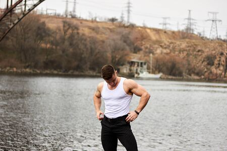 Attractive young guy demonstrates muscular torso outdoors. Beautiful physique. Fitness and lifestyle concept. Pronounced muscles of the press. Athletic physique. Banque d'images