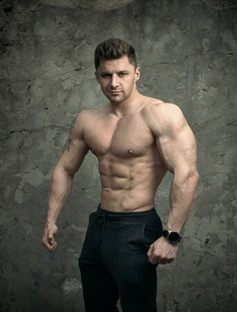 Handsome muscular man posing on concrete wall background. The concept of fitness, bodybuilding, health, lifestyle. Portrait of fitness fitness model.