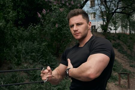 Athletic attractive guy is training outdoors. The concept of sports, health, fitness. Young man in a sports t-shirt.