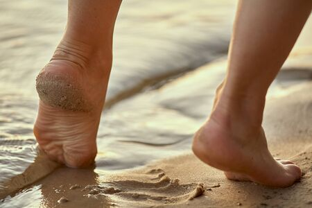 Female feet barefoot on a sandy beach in the water. Close-up of beautiful female legs. Wet foot. Stock fotó