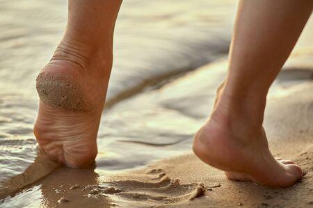 Weibliche Füße barfuß an einem Sandstrand im Wasser. Nahaufnahme der schönen weiblichen Beine. Nasser Fuß. Standard-Bild