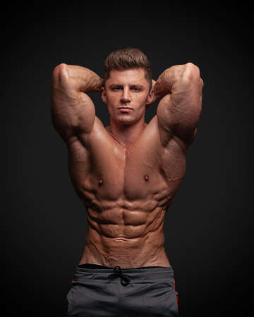 Muscular man bodybuilder isolated on a black background .. Male posing on a black background, shows his muscles. Bodybuilding, posing, black background, model.