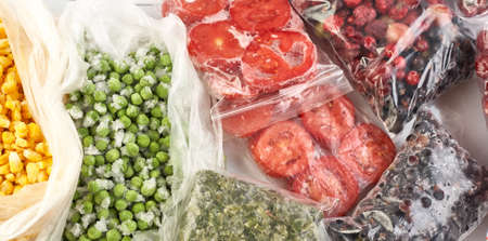 A set of frozen foods for the winter. Frozen berries, vegetables, corn, green peas, tomatoes in the freezer.