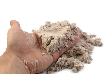 Hand and kinetic sand isolated on white background.