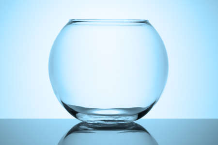 A round transparent empty aquarium stands on a reflective glass surface on a white background. Cold toned blue.